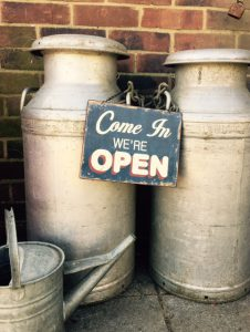 Come in we're open sign with milk churns